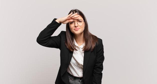 Jovem mulher de negócios parecendo perplexa e atônita, com a mão na testa olhando para longe, observando ou procurando