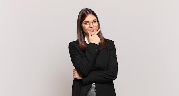 Jovem mulher de negócios parecendo séria, confusa, incerta e pensativa, duvidando de opções ou escolhas