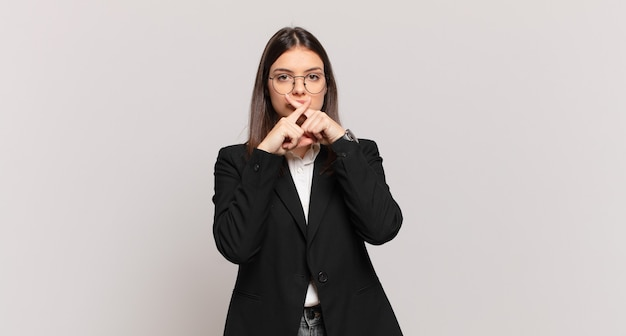 Jovem mulher de negócios parecendo séria e descontente com os dois dedos cruzados na frente em rejeição, pedindo silêncio