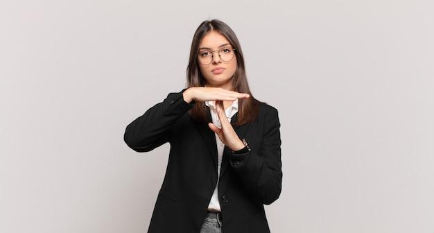 Jovem mulher de negócios parecendo séria, severa, zangada e descontente, fazendo sinal de castigo