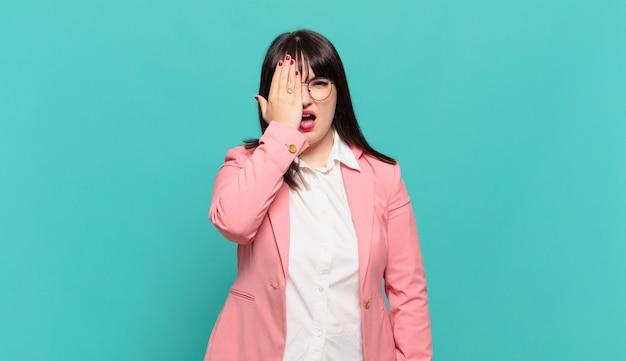 Jovem mulher de negócios parecendo sonolenta, entediada e bocejando, com dor de cabeça e uma das mãos cobrindo metade do rosto