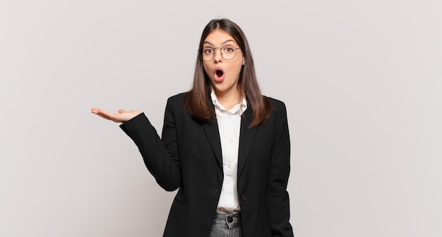 Jovem mulher de negócios parecendo surpresa e chocada, com o queixo caído segurando um objeto com a mão aberta na lateral
