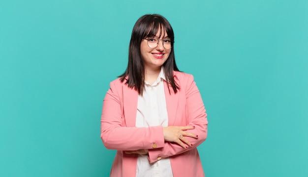 Jovem mulher de negócios parecendo uma empreendedora feliz, orgulhosa e satisfeita, sorrindo com os braços cruzados