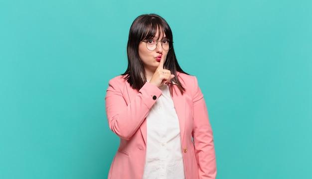 Jovem mulher de negócios pedindo silêncio e silêncio, gesticulando com o dedo na frente da boca, dizendo shh ou guardando um segredo
