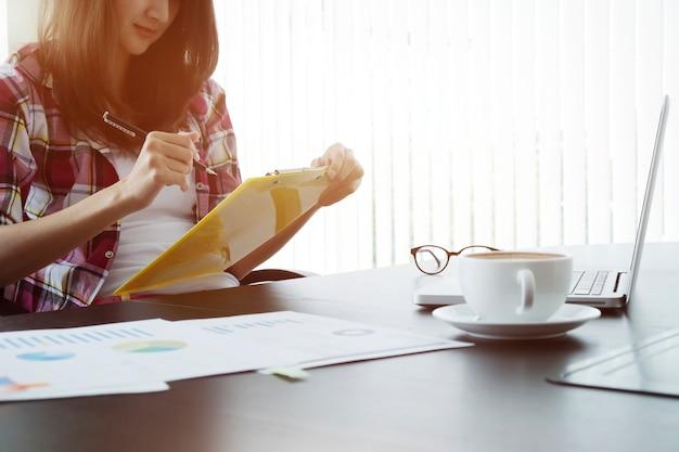 Jovem mulher de negócios que trabalha com um novo projeto de inicialização no escritório de coworking moderno.