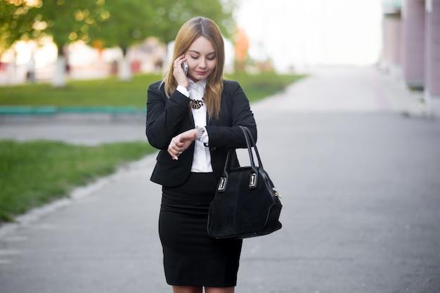 Jovem mulher de negócios que verifica o tempo no relógio de pulso
