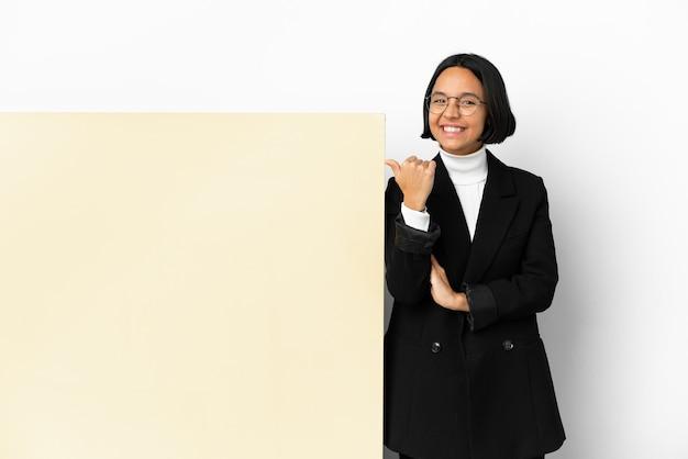 Jovem mulher de negócios, raça mista, com um grande banner sobre fundo isolado apontando para o lado para apresentar um produto