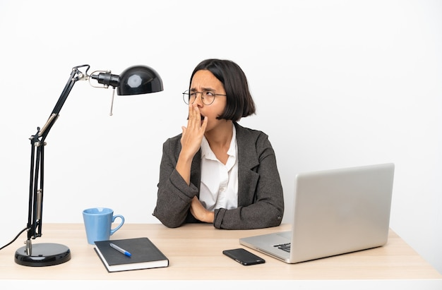 Jovem mulher de negócios, raça mista, trabalhando no escritório, bocejando e cobrindo a boca aberta com a mão