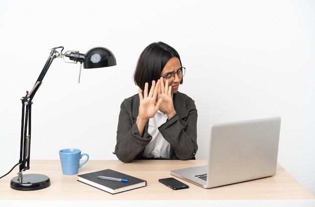 Jovem mulher de negócios, raça mista, trabalhando no escritório, nervosa, esticando as mãos para a frente