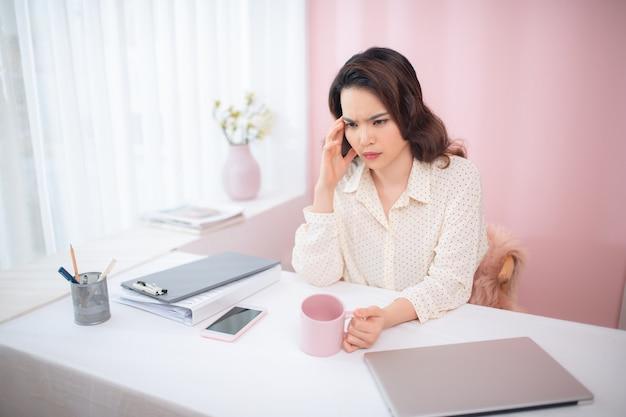 Jovem mulher de negócios se sentindo cansada e segurando a cabeça