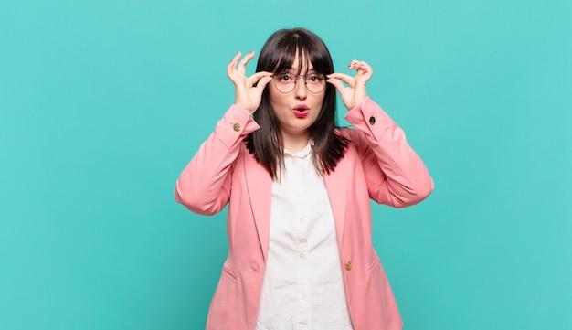 Jovem mulher de negócios se sentindo chocada, espantada e surpresa, segurando os óculos com ar espantado e incrédulo