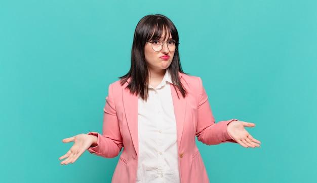 Jovem mulher de negócios se sentindo sem noção e confusa, sem fazer ideia, absolutamente perplexa com um olhar idiota ou tolo