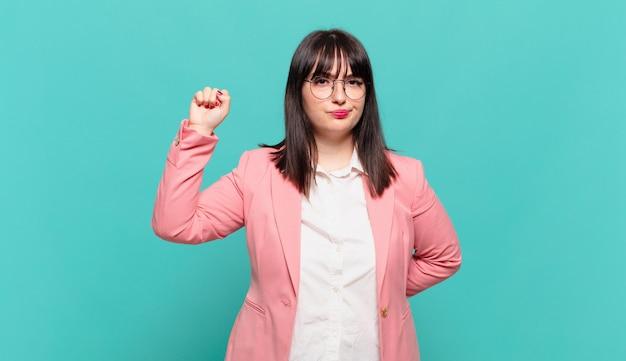 Jovem mulher de negócios se sentindo séria, forte e rebelde, levantando o punho, protestando ou lutando pela revolução