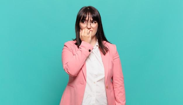 Jovem mulher de negócios se sentindo séria, pensativa e preocupada, olhando de lado com a mão pressionada contra o queixo