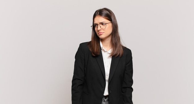 Jovem mulher de negócios se sentindo triste, chateada ou com raiva e olhando para o lado com uma atitude negativa, franzindo a testa em desacordo