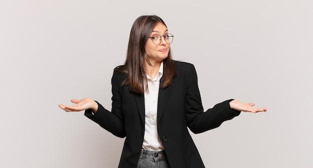 Jovem mulher de negócios sentindo-se perplexa e confusa, insegura sobre a resposta ou decisão correta, tentando fazer uma escolha