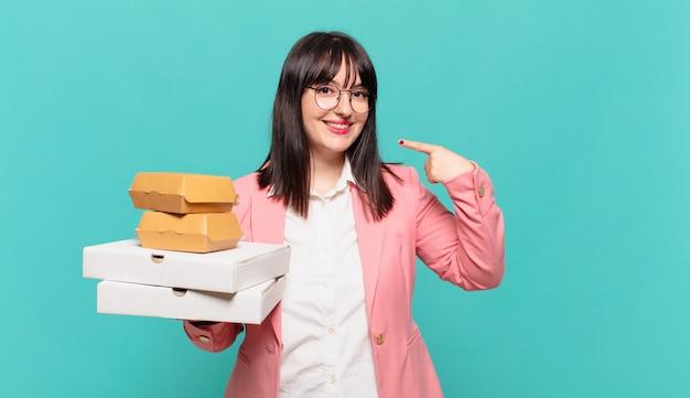Jovem mulher de negócios sorrindo com confiança apontando para o próprio sorriso largo, atitude positiva, relaxada e satisfeita