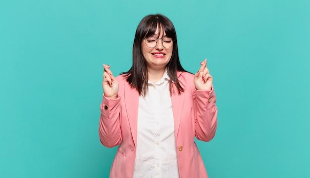 Jovem mulher de negócios sorrindo e cruzando os dedos ansiosamente, preocupada e desejando ou esperando por boa sorte
