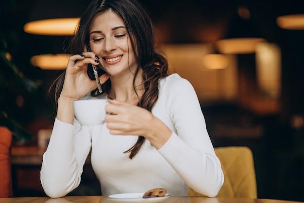 Jovem mulher de negócios tomando café em um café