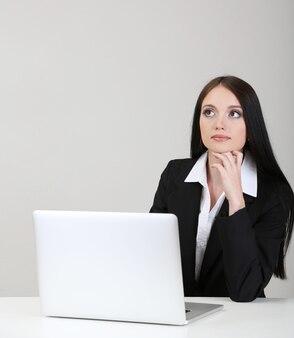 Jovem mulher de negócios trabalhando com computador, em cinza