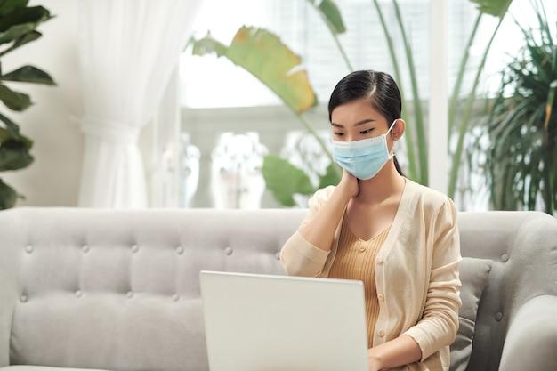 Jovem mulher de negócios trabalhando em casa com um laptop e usando máscara protetora