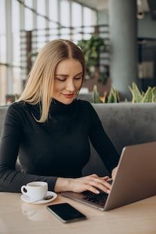 Jovem mulher de negócios trabalhando em um laptop em um café