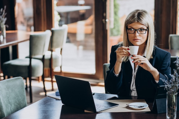 Jovem mulher de negócios trabalhando no computador em um café