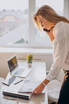 Jovem mulher de negócios usando telefone no escritório