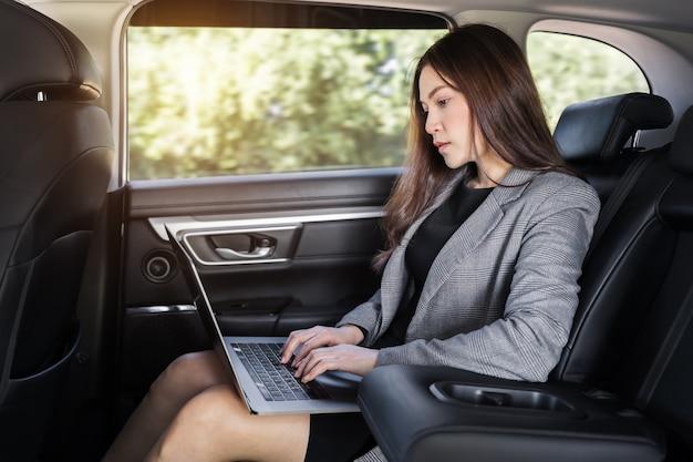 Jovem mulher de negócios usando um laptop enquanto está sentada no banco de trás do carro