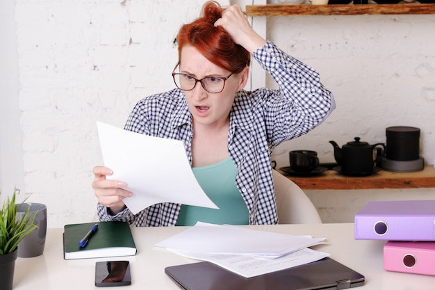 Jovem mulher de óculos com cabelo curto ruivo fica chocada com o que vê nos documentos oficiais