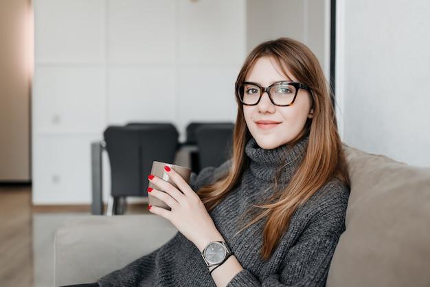 Jovem mulher de óculos sentado com copo no sofá em casa no apartamento a sorrir