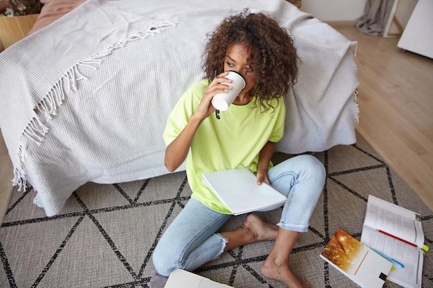 Jovem mulher de pele escura com cabelo castanho cacheado estudando em casa com livros e caderno, fazendo uma pausa e tomando café