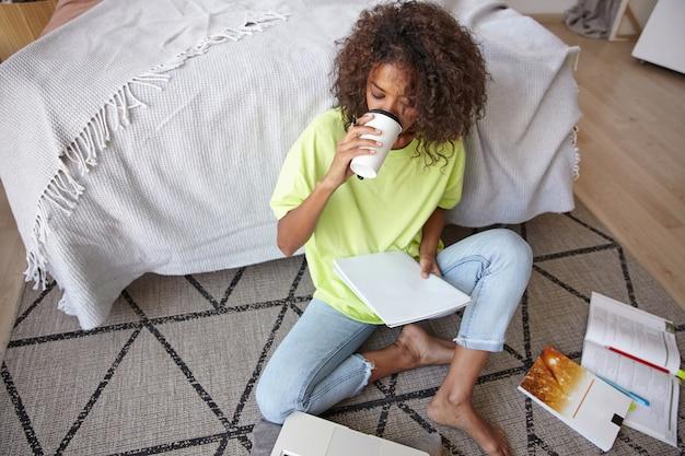 Jovem mulher de pele escura com cabelo castanho cacheado, estudando em casa, sentada no tapete com estampa geométrica, bebendo café e olhando suas anotações