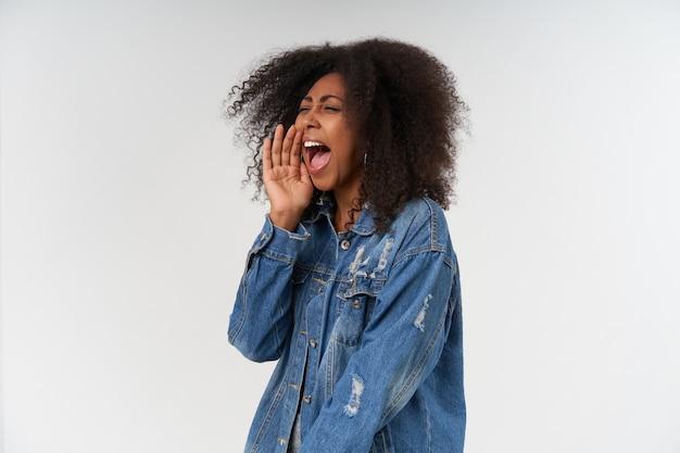 Jovem mulher de pele escura e encaracolada com top branco e casaco jeans em pé sobre a parede branca, olhando para o lado e levando a palma da mão à boca enquanto grita algo