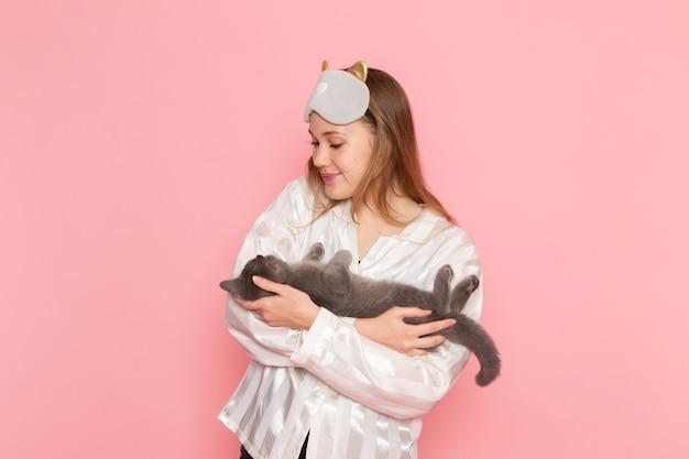 Jovem mulher de pijama e máscara de dormir posando com um gatinho cinza fofo na rosa