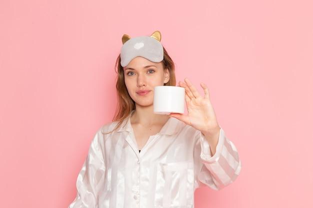 Jovem mulher de pijama e máscara de dormir segurando creme com um sorriso rosa