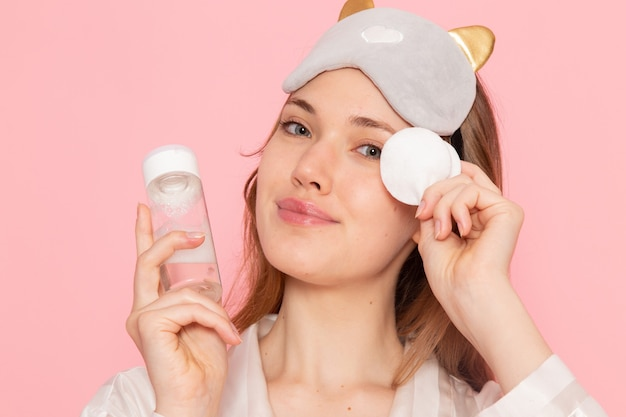 Jovem mulher de pijama e máscara de dormir segurando spray rosa