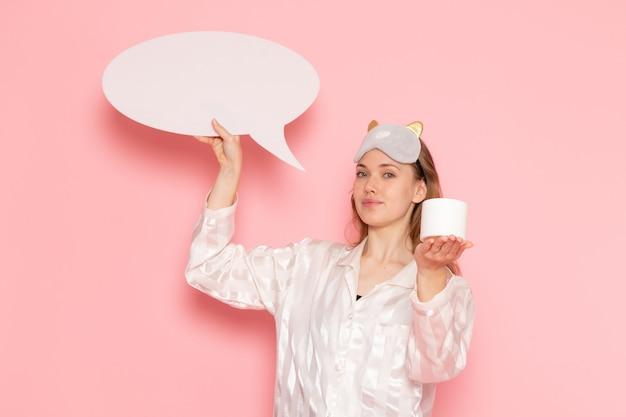 Jovem mulher de pijama e máscara de dormir segurando um cartaz branco em creme rosa