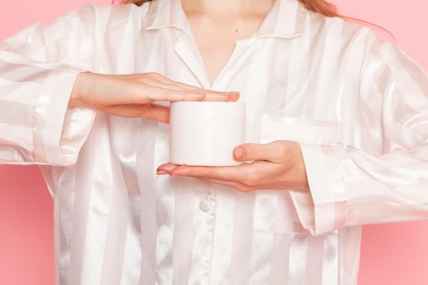 Jovem mulher de pijama e máscara de dormir segurando uma lata de creme branca sobre rosa