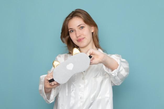 Jovem mulher de pijama e máscara de dormir sorrindo e posando em azul