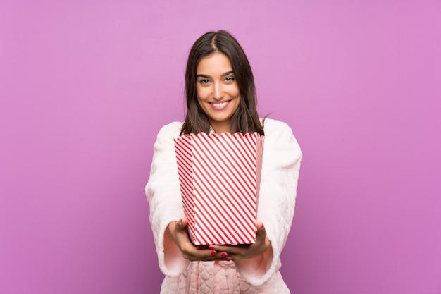 Jovem mulher de pijama e roupão sobre fundo roxo isolado segurando pipocas