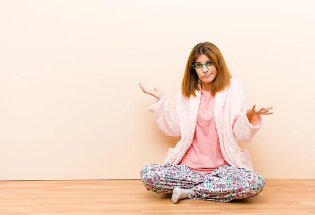 Jovem mulher de pijama, sentada em casa, encolher os ombros com uma expressão idiota, louca, confusa e confusa, sentindo-se irritada e sem noção
