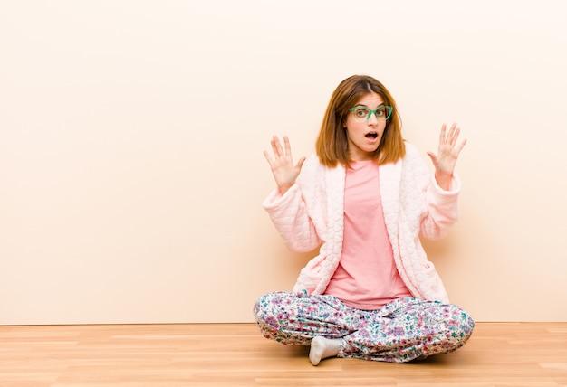 Jovem mulher de pijama, sentada em casa, sentindo-se estupefata e assustada, temendo algo assustador, com as mãos abertas dizendo que fique longe