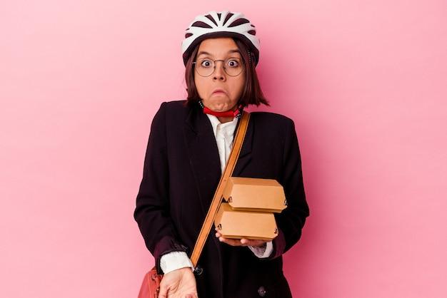 Jovem mulher de raça mista com capacete de bicicleta segurando hambúrguer isolado na parede rosa encolhe os ombros e abre os olhos confusos