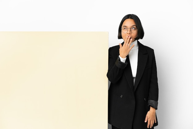Jovem mulher de raça mista com um grande banner sobre um fundo isolado, bocejando e cobrindo a boca aberta com a mão