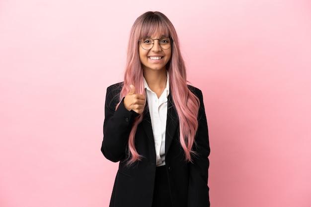 Jovem mulher de raça mista, negócios, com cabelo rosa isolado em um fundo rosa fazendo um gesto de polegar para cima