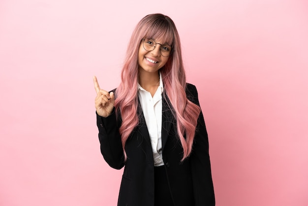 Jovem mulher de raça mista, negócios, com cabelo rosa isolado em um fundo rosa, mostrando e levantando um dedo em sinal dos melhores