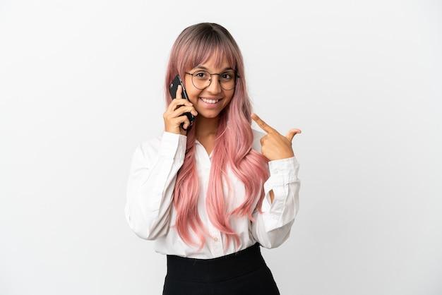 Jovem mulher de raça mista, negócios, com cabelo rosa segurando um celular isolado no fundo rosa e fazendo um gesto de polegar para cima