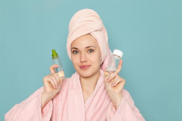 Jovem mulher de roupão rosa segurando frascos de maquiagem em azul