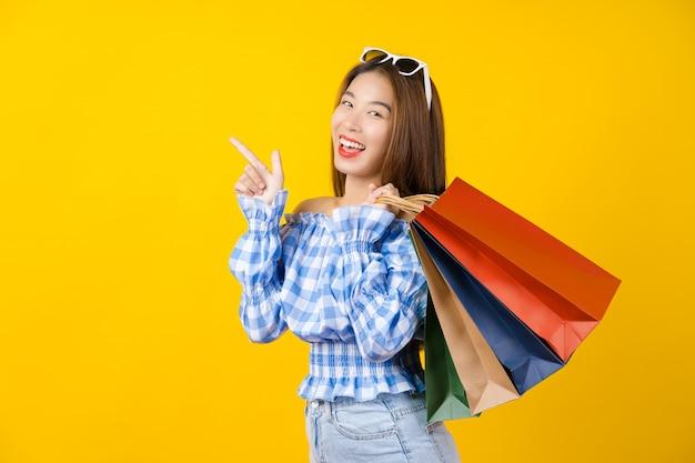 Jovem mulher de sorriso asiática atrativa que leva um saco coloful da compra e que aponta a propaganda da venda na parede, espaço da cópia e estúdio amarelos isolados, conceito preto da venda da estação de sexta-feira.